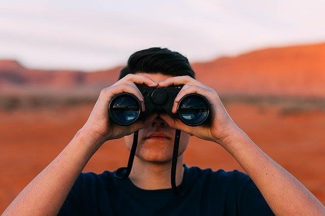 man looking with binoculars